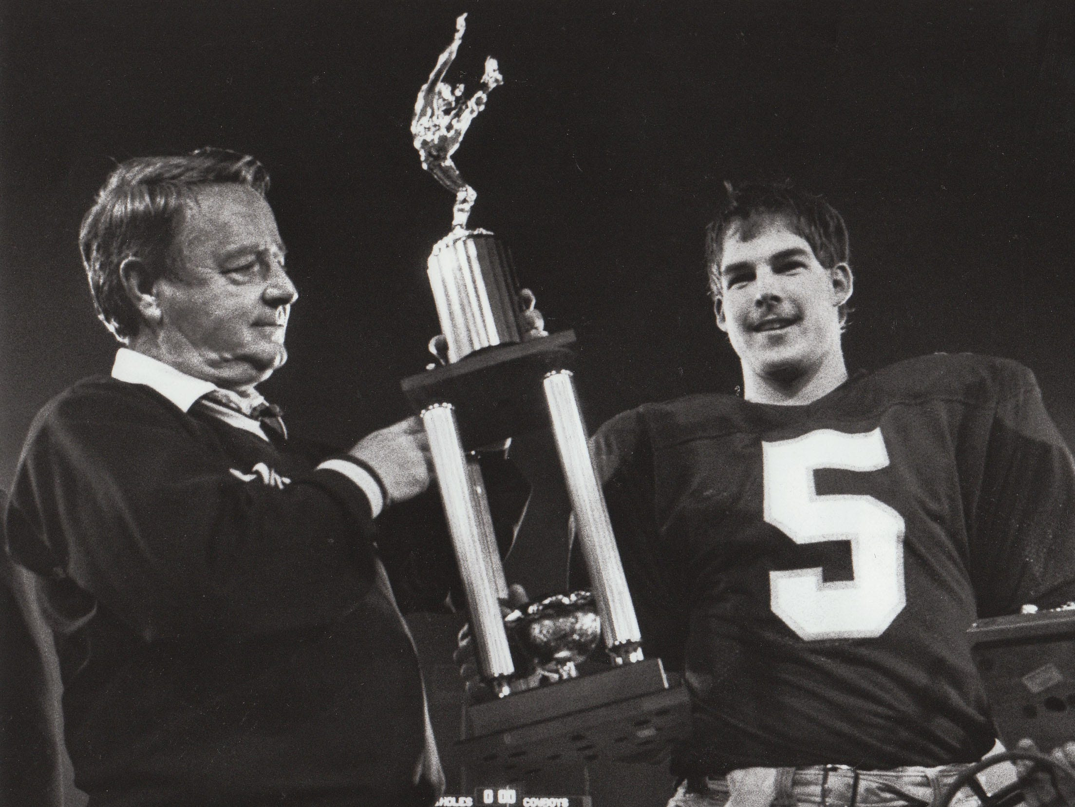 Bobby Bowden and Chip Ferguson hoist the Gator Bowl trophy in 1985 after Ferguson was named the game's MVP.