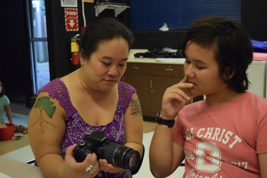 Casey Yu, left, shows her son Matthew Burnett, a seventh grader at Cobb Middle School, features on a DSLR camera. Yu is a first year teacher at Cobb Middle School.