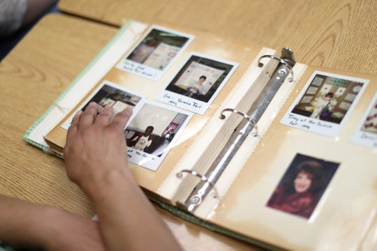 Beverly Robinson, who will be starting her last year as a teacher at Kate Sullivan Elementary School after joining the staff there in 1990, looks through a book of photos of her students over the years from her classroom on Friday, Aug. 10, 2018.