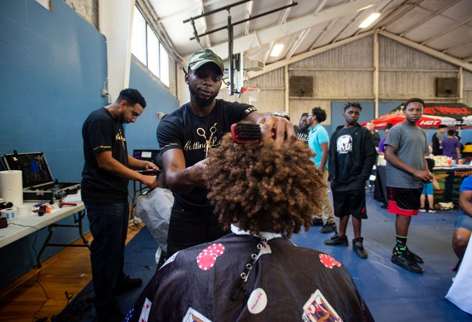 "Malivert Steven, a barber with Cutting Loose in Port St. Lucie, gives a free haircut to Fort Pierce Westwood High School incoming freshman Josh Becerra, 16, during the Back to School Bash on Friday, Aug. 10, 2018, at the Police Athletic League on South 21st Street in Fort Pierce. Wydee'a Wilson, chief probation officer for the Florida Department of Juvenile Justice in Circuit 19, said, ""DJJ are hosting this event, thanks to many, many organizations in the community — especially LifeBuilders, which is the public defender Diamond Litty's nonprofit organization."" The event's theme was ""eliminating the school to prison pipeline,"" and featured free food, entertainment, school supplies, games and prizes, as well as information and services from local groups and vendors."