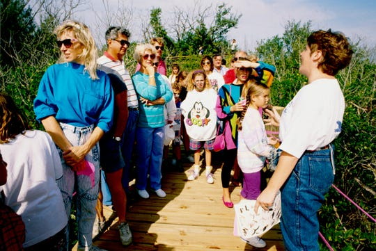 November 14, 1992 - The Environmental Learning Center held its grand opening with a lagoon discovery day for area residents to enjoy. In addition to booths, live entertainment and boat rides, Sue DeBlois (far right) was one of many guides giving tours throughout the mangrove area on the boardwalk behind the center.
