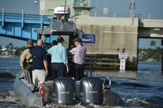 Florida Governor Rick Scott (right) and Senator Joe Negron (center) pass under the old Roosevelt Bridge while touring the algae affected areas of the St. Lucie River from a Florida Fish and Wildlife Conservation boat on Friday, August 10, 2018, in Stuart.