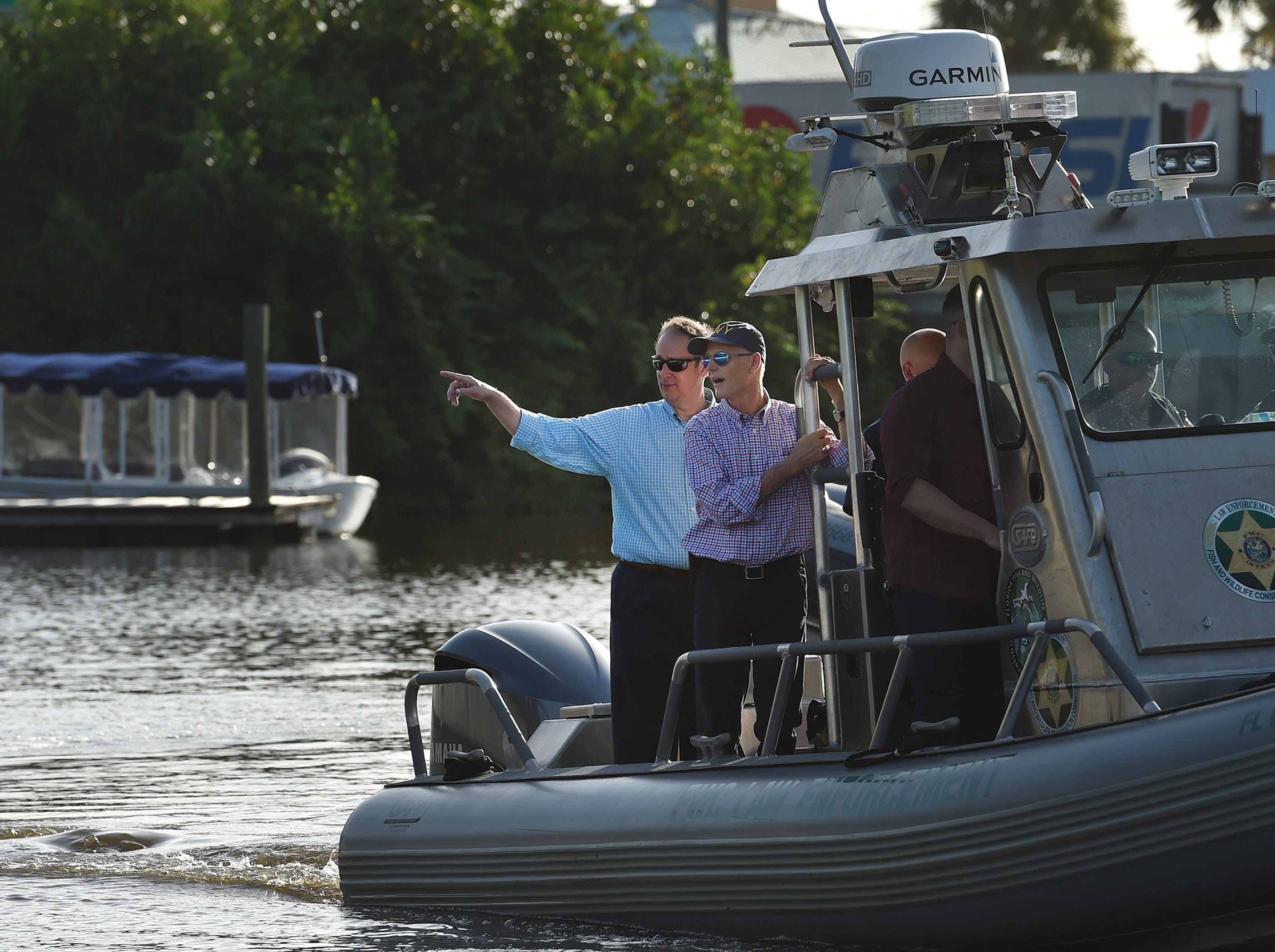Senator Joe Negron (from left) and Governor Rick Scott tour the algae affected areas of the St. Lucie River from a Florida Fish and Wildlife Conservation boat on Friday, August 10, 2018, in Stuart.