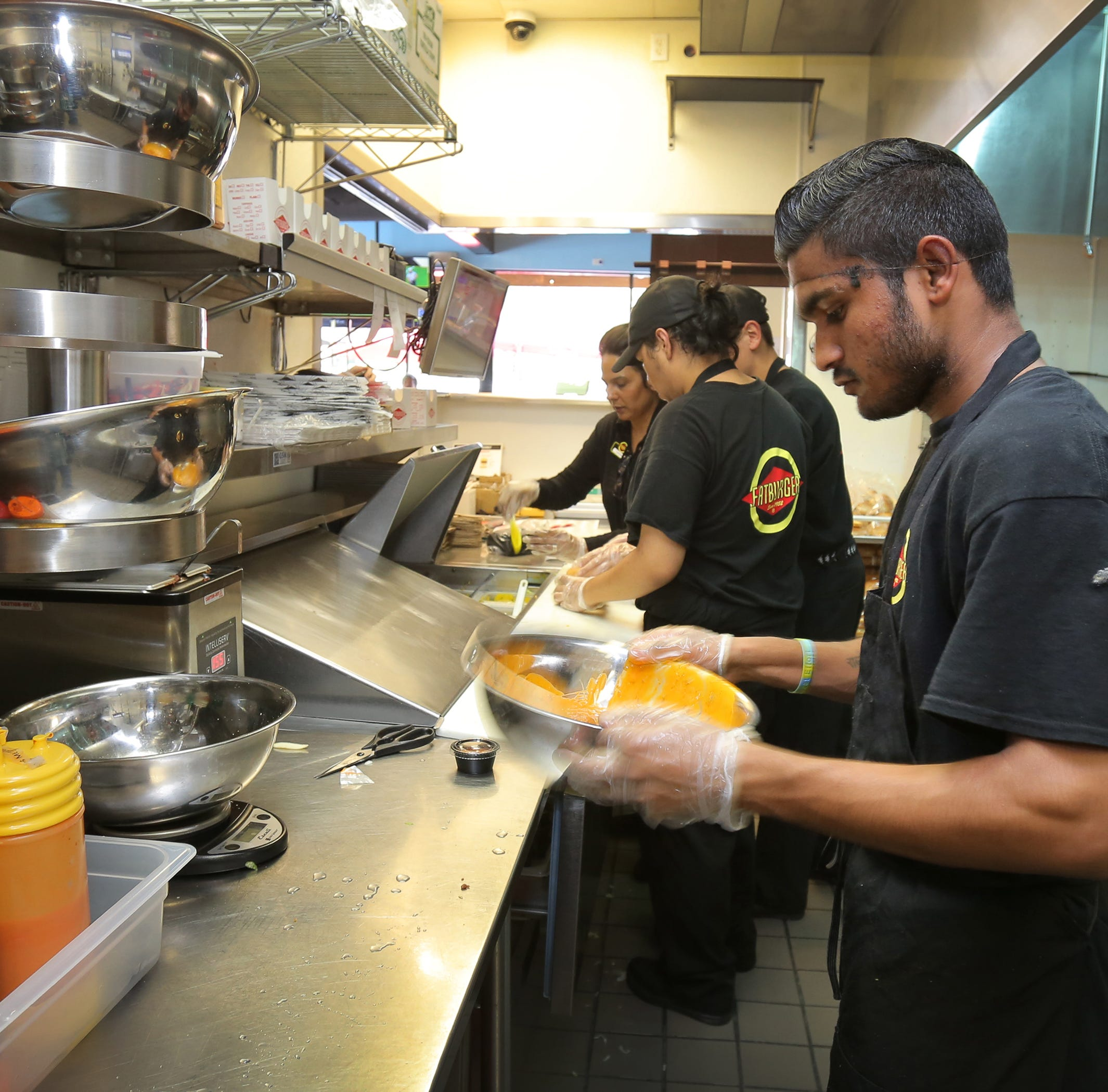 Raj Singh works on an order of chicken wings as Micheal Lopez, manager Jasbir Kaur and Antonio Ortiz prepare hamburgers at the Fatburger & Buffalo's Express that recently opened in Thousand Oaks.