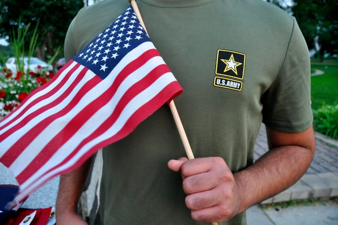 In this July 3 photo, a Pakistani recruit who was recently discharged from the U.S. Army holds an American flag as he poses for a picture. The U.S. Army has stopped discharging immigrant recruits who enlisted seeking a path to citizenship, at least temporarily.