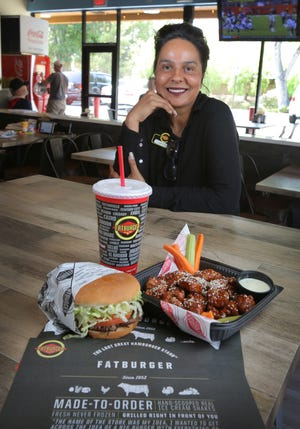 Fatburger & Buffalo's Express manager Jasbir Kaur sits with two of the restaurant's popular items — a large burger with the works and boneless Asian Sesame Chicken Wings in the Thousand Oaks eatery.