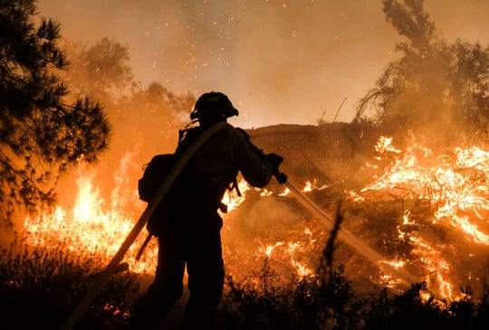 A firefighter battles the Holy Fire burning in the Cleveland National Forest along a hillside at Temescal Valley in Corona on Thursday.