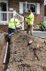 A crew from Rockland Electric temporarily restores power to the Temple Lane home of Joan Frank in Suffern on Friday, August 10, 2018.  Floods over the years corroded the underground electrical lines to the home causing them to fail.  The home is set to be demolished next month.