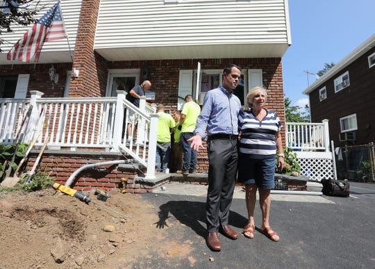 New York Senator David Carlucci, center stands with Suffern resident Joan Frank in front of her Temple Lane home as a crew from Rockland Electric temporarily restore power to the house on Friday, August 10, 2018.