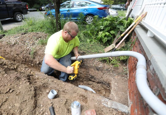 Electrician Michael Johns from Rockland Electric works on the conduit to restore temporary power to the home of Joan Frank on Temple Lane. in Suffern on Friday, August 10, 2018.