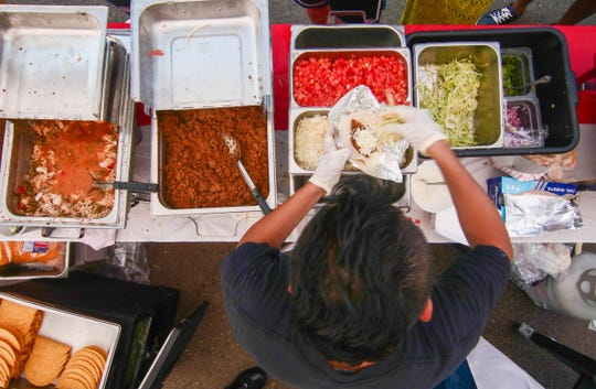 A Mexican Post cook prepares a taco during the Delaware Taco Festival, which returns to Wilmington's Frawley Stadium on Saturday.