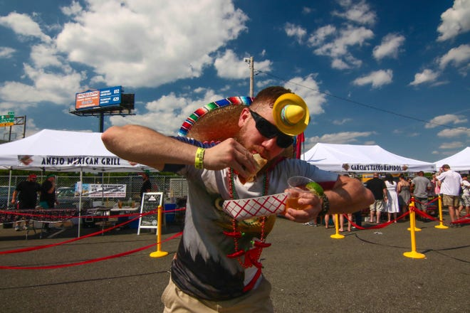 Andrew Rossi bites into a taco during the Delaware Taco Festival, which returns to Wilmington this weekend.