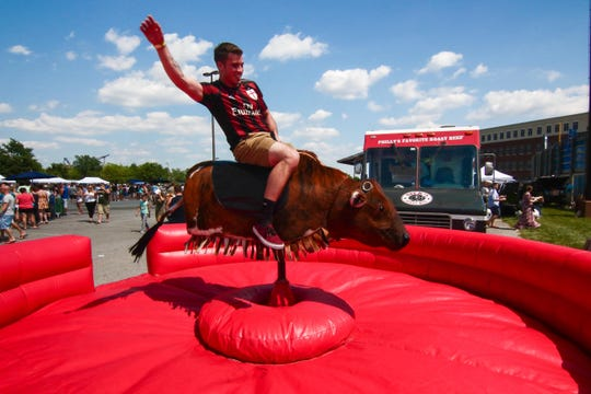 Connor Fawzi of Pennsylvania rides the mechanical bull during the first Delaware Taco Festival in 2016.