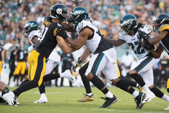 Eagles defensive end Michael Bennett, center, tries to get around Pittsburgh's Jesse James (81) Thursday at Lincoln Financial Field.