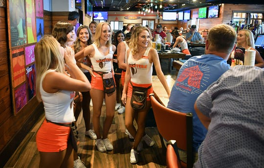 A group of Hooters Girls gather at the bar to perform a short song for a patron's birthday. The Hooters sports bar and restaurant opened this week in the old Logan's Roadhouse location on Call Field Road.