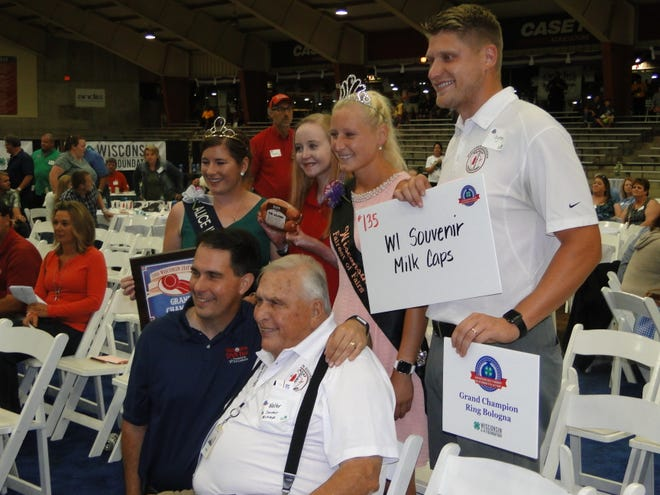 Former Gov. Scott Walker congratulates Wally Bohrer, a longtime supporter of both the Governor's Meat Products Auction and the Governor's Livestock Auction, during the Aug. 7, 2019 Governor's Blue Ribbon Meat Products auction. Joining them are Boher's grandchild, Dayton Young, Alice in Dairyland Kaitlyn Riley and Fairest of the Fair Isabella Haen.