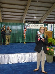 Wisconsin 4-H Leadership Council youth President Libby Wilkomm encourages bidders to buy the award winning summer sausage at the Wisconsin Meat Processor's and Wisconsin 4-H Foundation meat products auction at the Wisconsin State Fair. Behind her Governor Scott Walker helps auctioneer Bob Johnson solicit the bids.