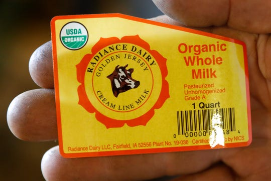 Organic dairy farmer Francis Thicke holds the label for milk produced on his farm in Fairfield, Iowa. Small family operated organic dairy farms with cows freely grazing on verdant pastures are going out of business while large confined animal operations with thousands of animals are expanding.