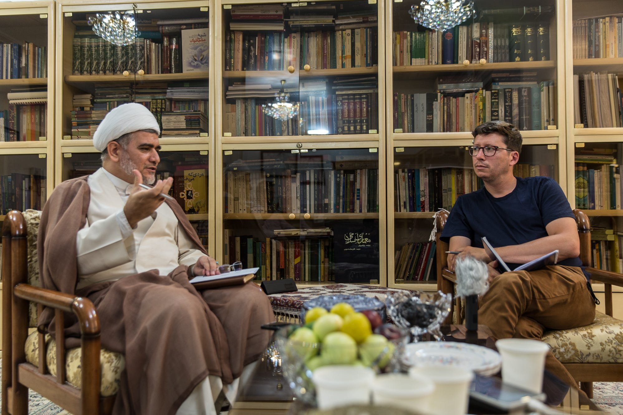 Mohsen Alviri, left, a cleric and religious scholar, converses with USA TODAY reporter Kim Hjelmgaard in his office in Qom, Iran, on July 12, 2018.