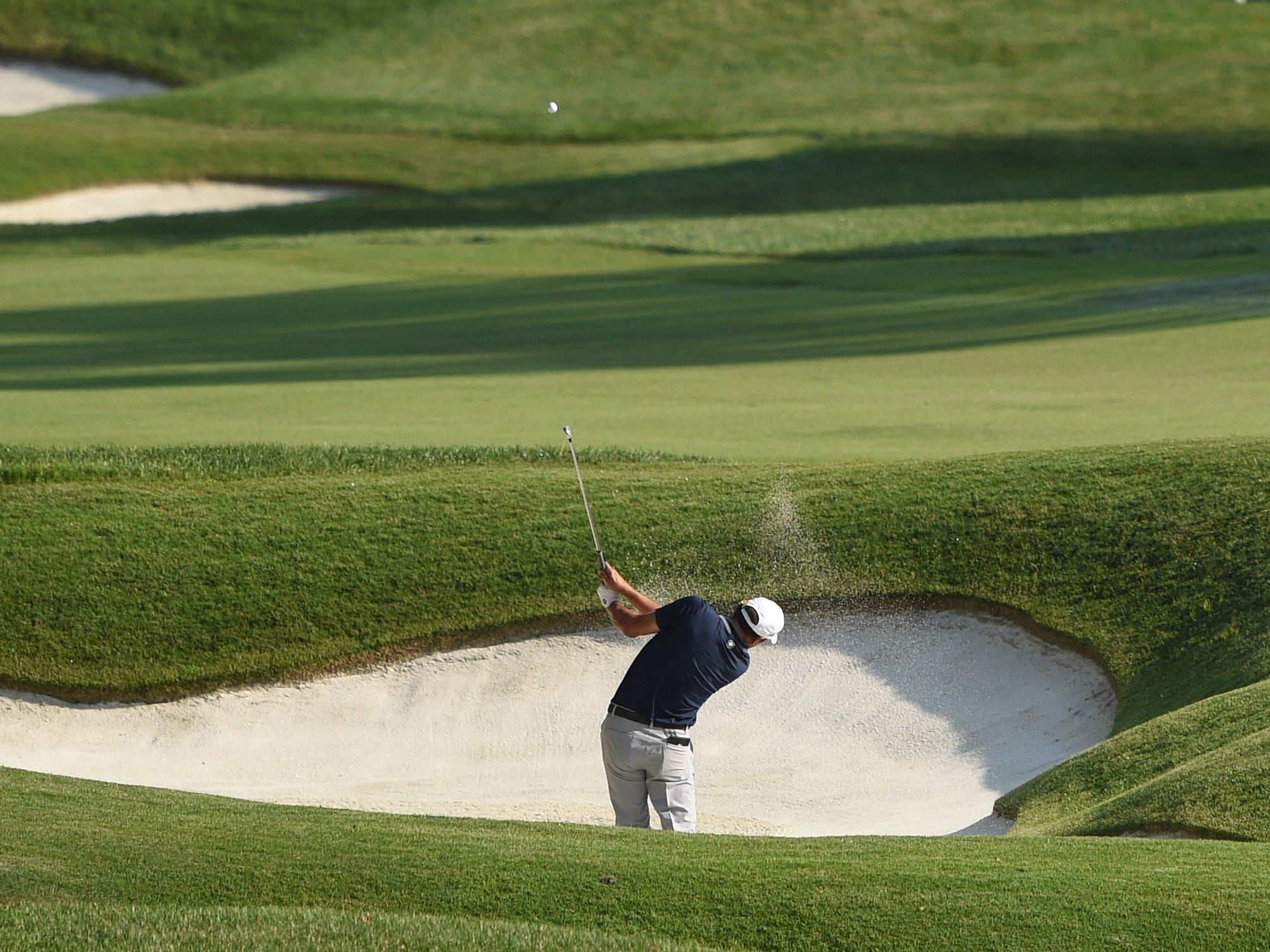 Johan Kok hits out of a bunker on the 18th hole during the second round.