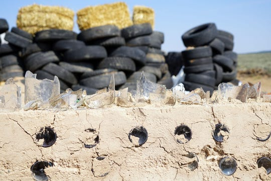 Broken glass embedded in the top of a mud wall built by adults living in a compound in Amalia, New Mexico, fronting a secondary wall made of dirt-filled tires.