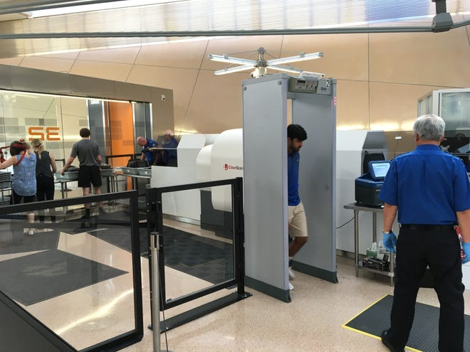 A traveler walks through a TSA metal-detector at Washington Dulles International Airport on Aug. 10, 2018, after placing his carry-on bags through a 3D scanner the TSA is testing. TSA is testing the computed tomography (CT) machines at 15 airports nationwide, with a goal of replacing all 2,000 standard X-ray machines with the 3D machines that allow a screener to rotate the image digitally to scrutinize suspicious items.