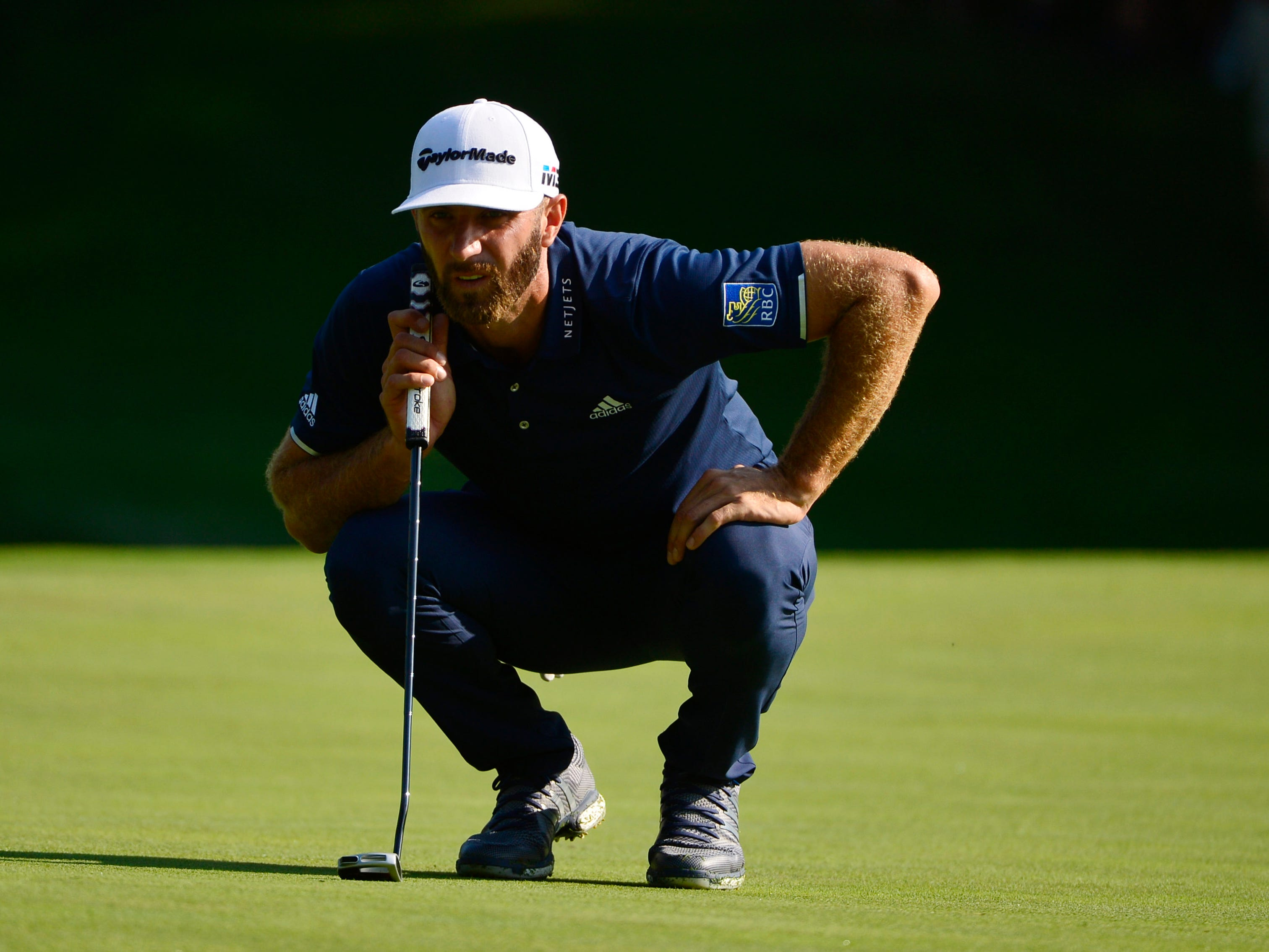 Dustin Johnson lines up a putt on the 15th green during the second round.