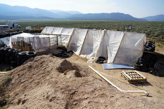 A compound in Amalia, New Mexico, where authorities say they rescued 11 kids and arrested five adults on suspicion of child abuse. This picture shows a partially buried RV, which has been covered by a plastic tarp, and a portion of the tire wall on the front of the site.