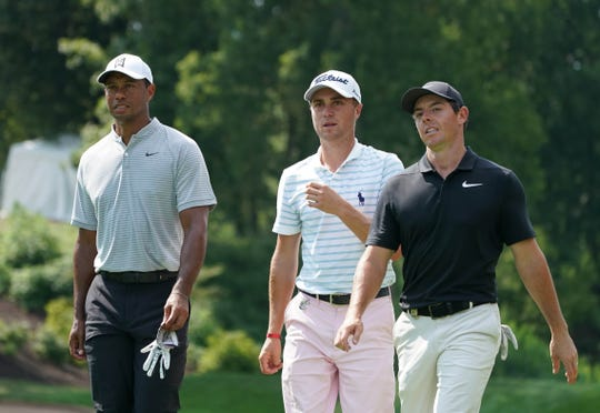 Tiger Woods , Justin Thomas and Rory McIlroy walk off the 8th tee during the second round.