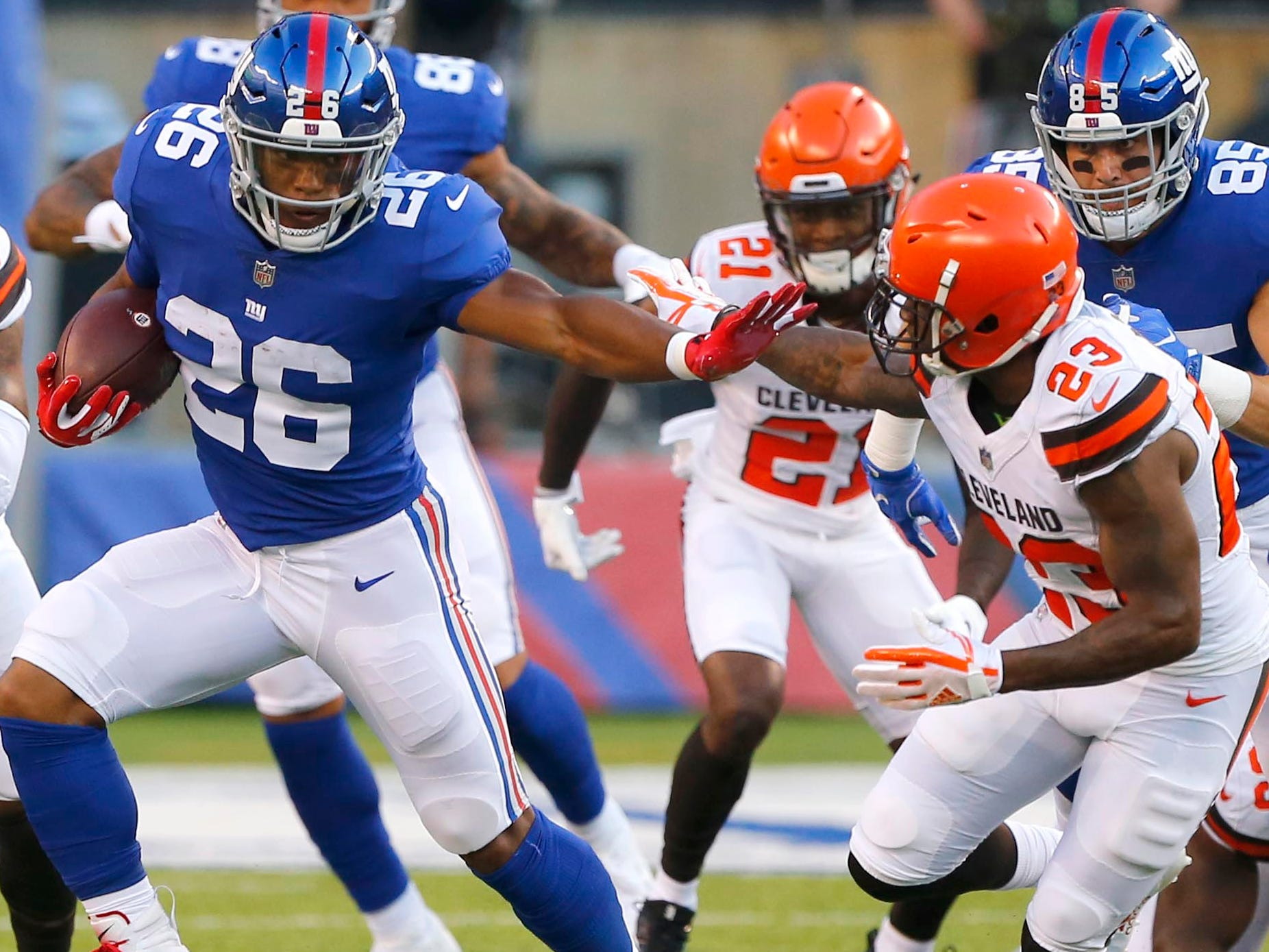 New York Giants running back Saquon Barkley (26) rushes against Cleveland Browns defensive back Damarious Randall (23) during first half at MetLife Stadium.