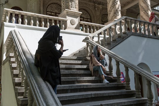 A woman takes a photograph of a friend as they wait on the stairs outside the entrance to the Cinema Museum of Iran, in Tehran on July 15, 2018.