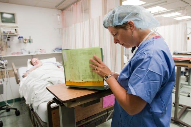 A nurse reviews a patient's chart.
