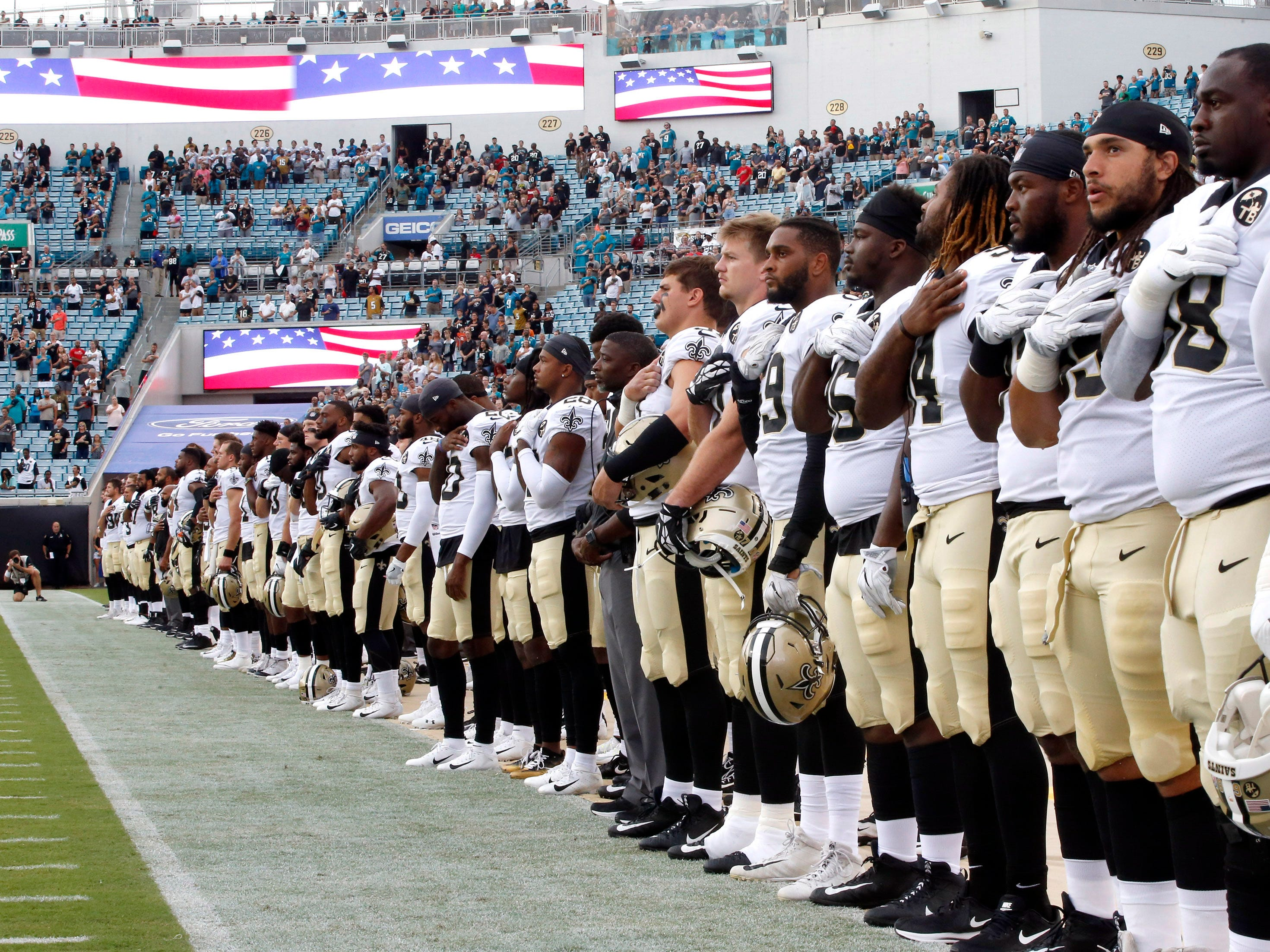 The New Orleans Saints players stand for the national anthem before a game against the Jacksonville Jaguars  at TIAA Bank Field.