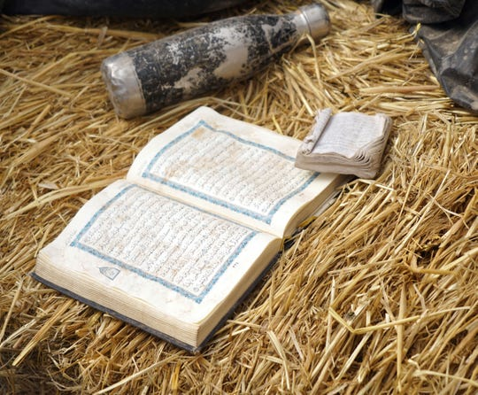 A Quran, along with an English-language translation, sit next to a battered water bottle inside the compound at Amalia, New Mexico, where authorities arrested five adults on suspicion of child abuse.