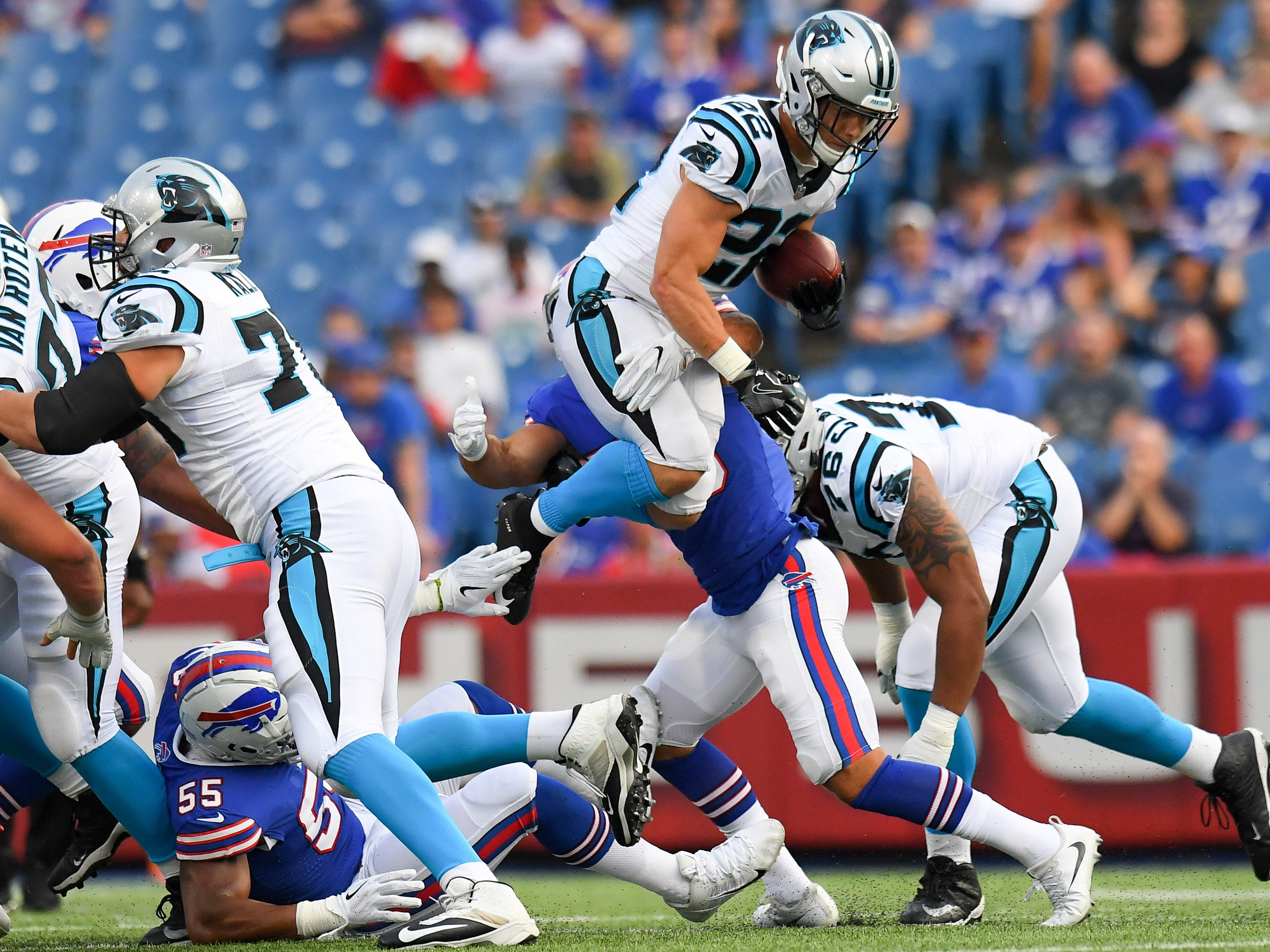 Carolina Panthers running back Christian McCaffrey (22) leaps while running with the ball against the Buffalo Bills during the first quarter at New Era Field.