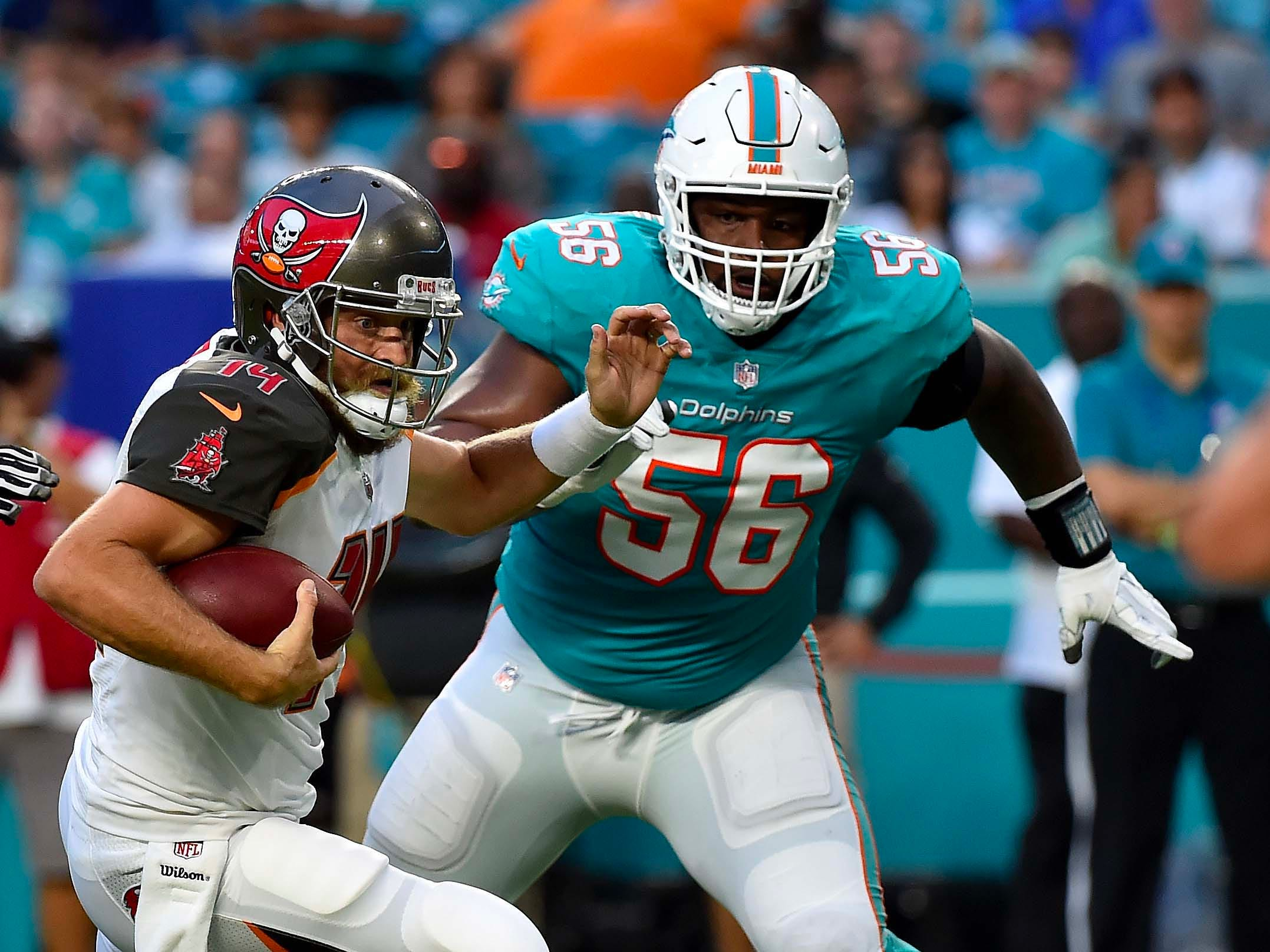 Miami Dolphins defensive tackle Davon Godchaux (56) closes in on Tampa Bay Buccaneers quarterback Ryan Fitzpatrick during the first half at Hard Rock Stadium.