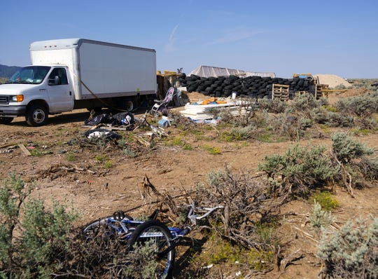 A broken child's bike, a stroller and piles of trash sit on the ground near a moving truck used as a makeshift dormitory for several people found living in a fortified compound in Amalia, New Mexico. Adults living at the compound built a wall out of dirt-filled tires, and another wall out of mud bricks studded with broken glass.