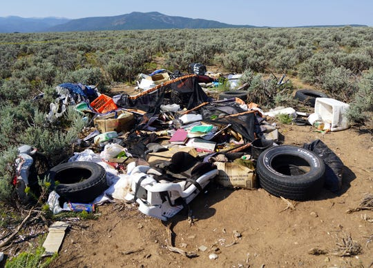 A collapsed tent, books and a child's car seat are among the items strewn about a compound in Amalia, New Mexico, following a law enforcement raid that ended with the arrest of five adults on child-abuse charges and 11 children being rescued.
