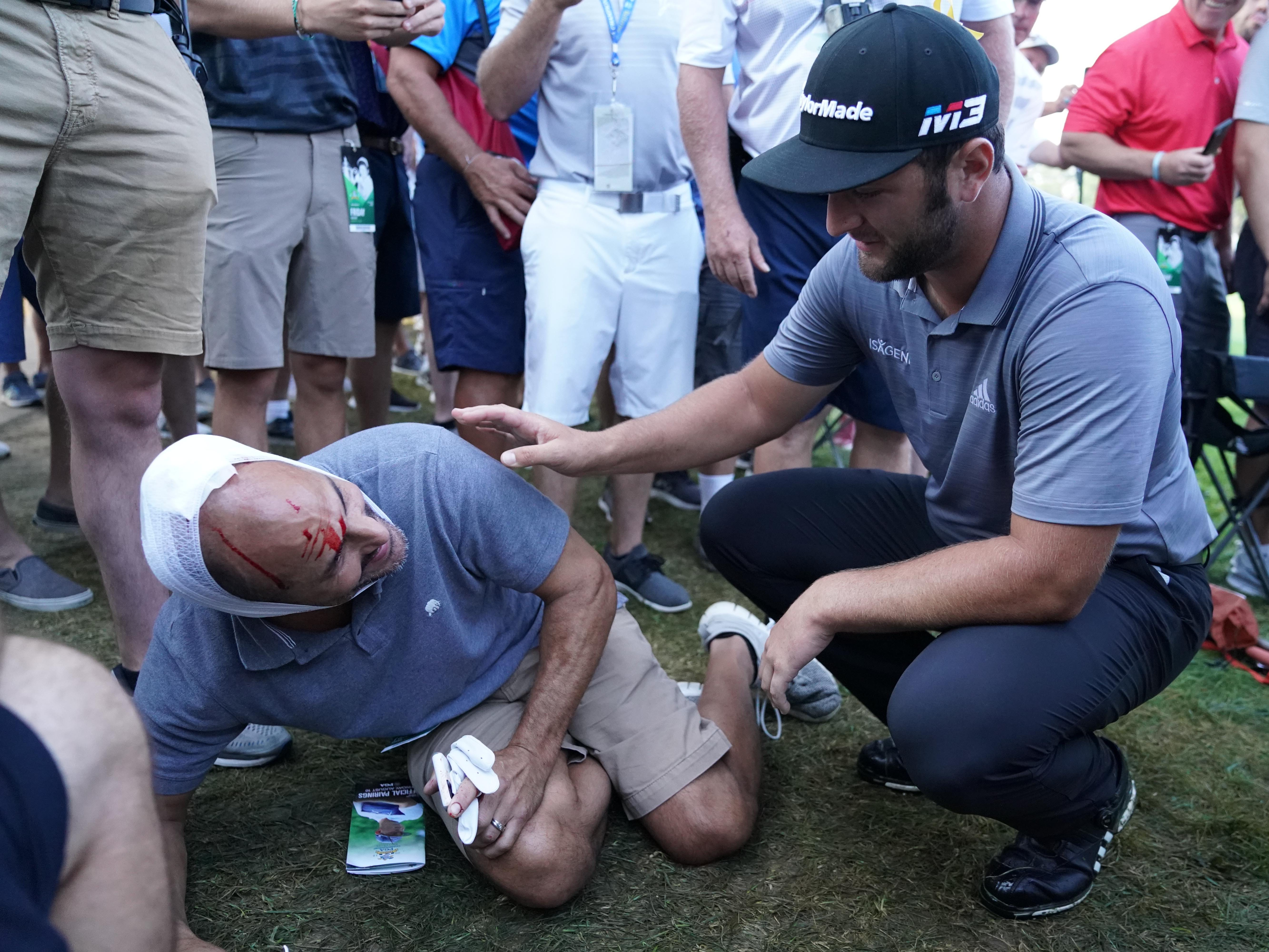 Golf fan Donald Hayden is checked on after being hit by a ball from Jon Rahm on the 10th hole during the second round.