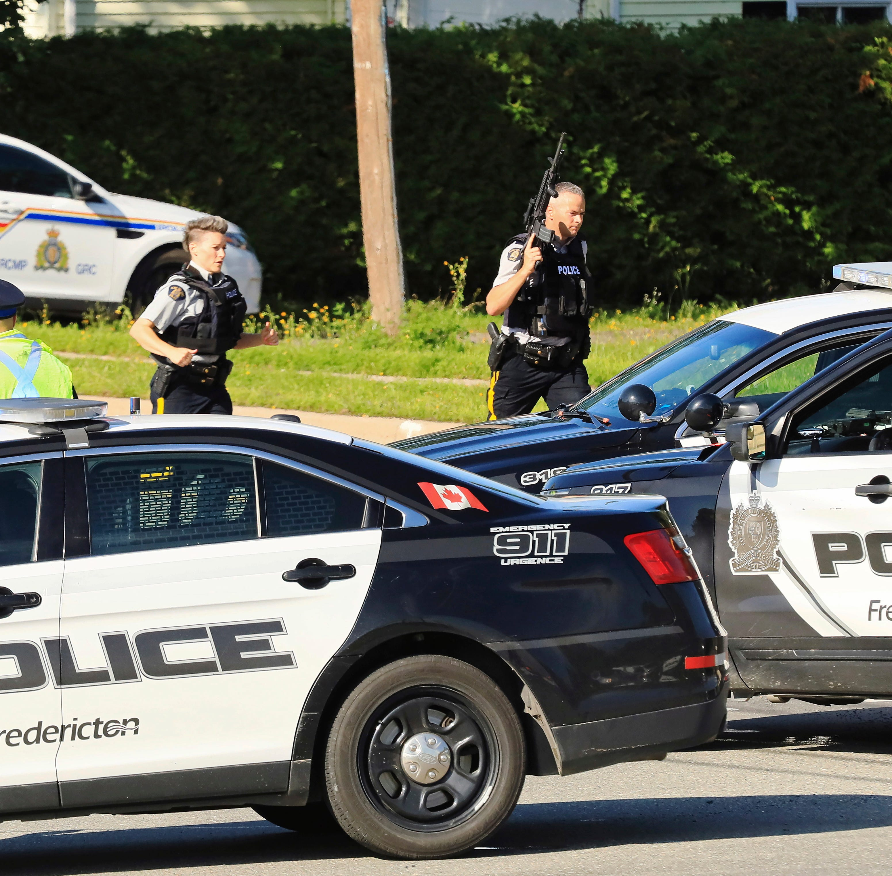Police and RCMP officers survey the area of a shooting in Fredericton, New Brunswick, Canada on  Aug.  10, 2018.  Fredericton police say two officers were among four people who died in a shooting in a residential area on the city's north side. One person was in custody, they said.