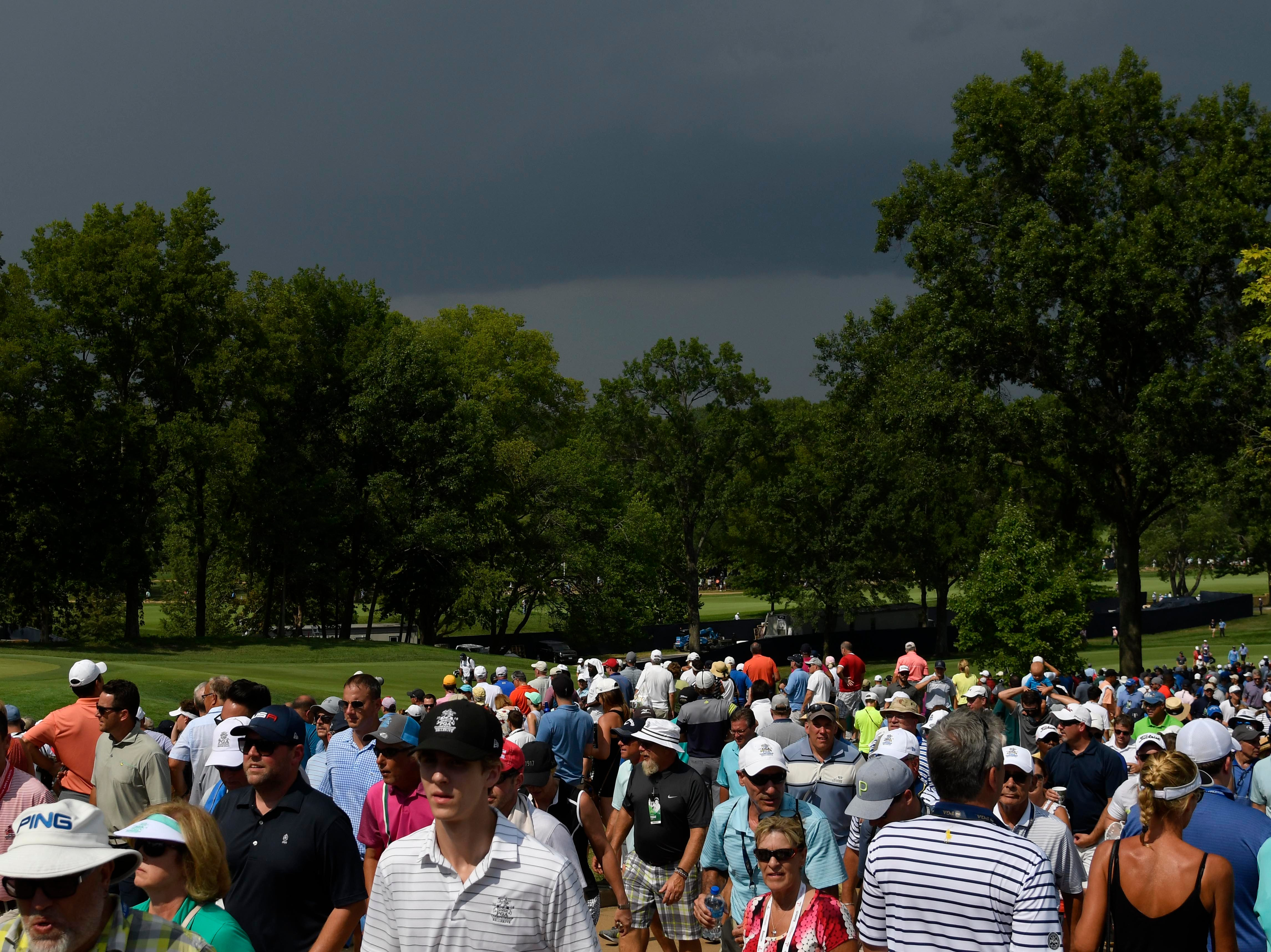 Fans begin to head to shelter as dark clouds move in for a weather delay during the second round.