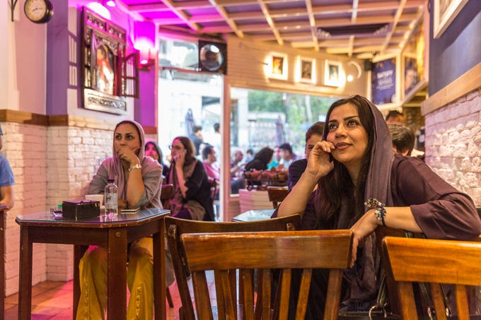 Patrons of a cafe in Tehran, Iran, watch a television screen (not shown), on July 15, 2018.