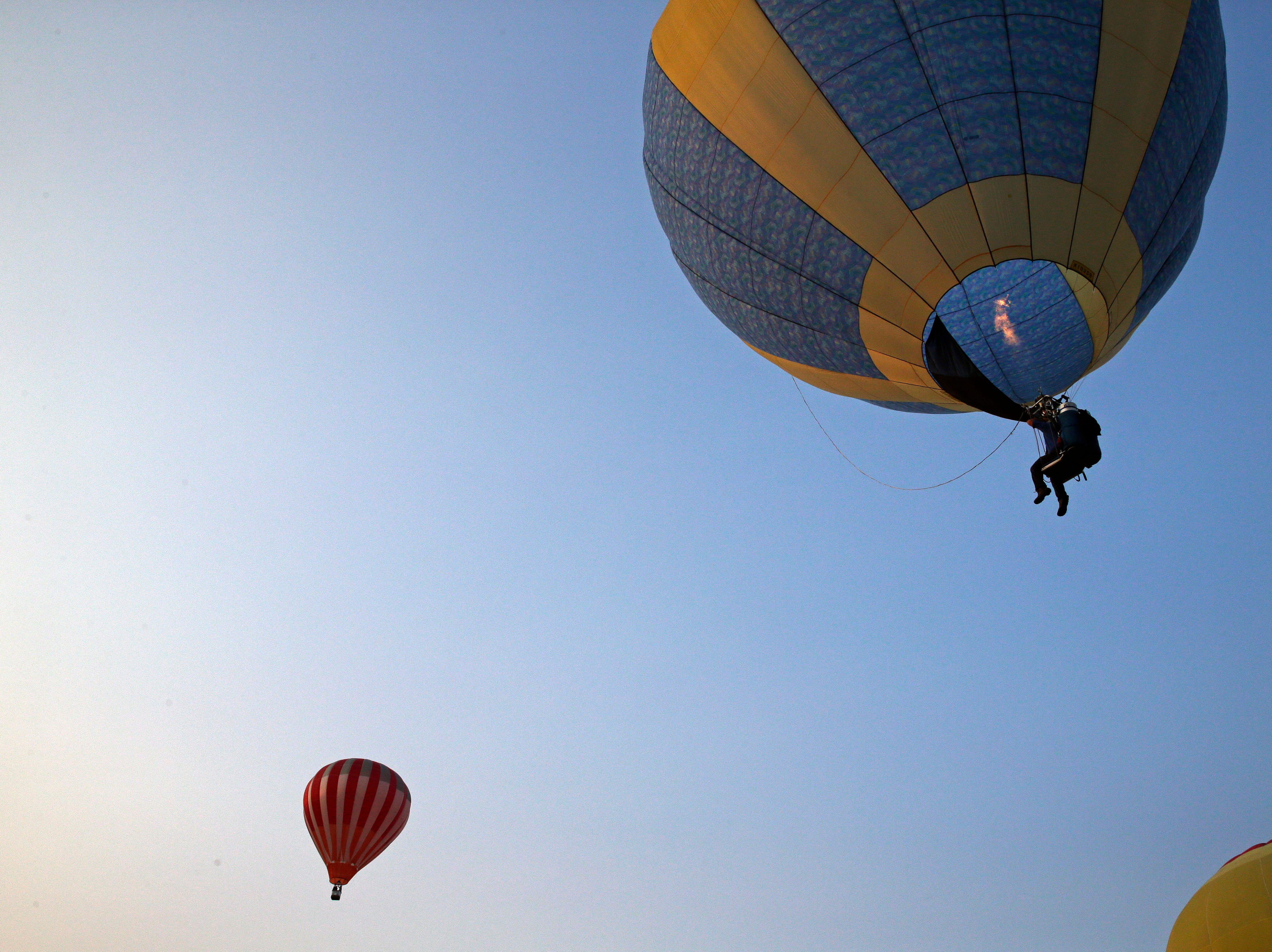 Dave Koenig of Menasha sits in a chair rather than a basket as he takes part in a hot air balloon ascension during the 30th annual Burger Fest Saturday, August 11, 2018, in Seymour, Wis.