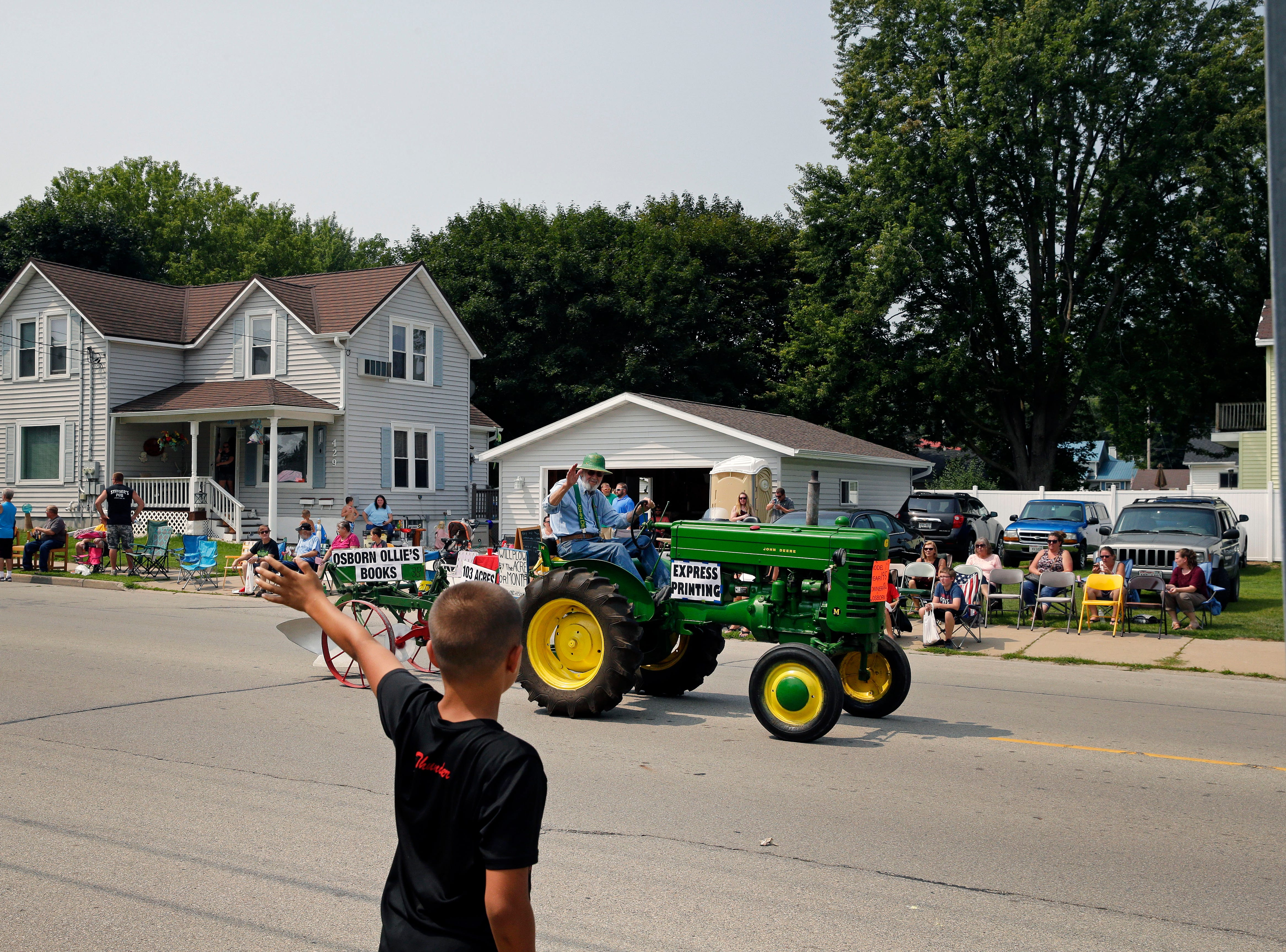 Micah Byers has a wave for a participant during the Hamburger Parade at the 30th annual Burger Fest Saturday, August 11, 2018, in Seymour, Wis.