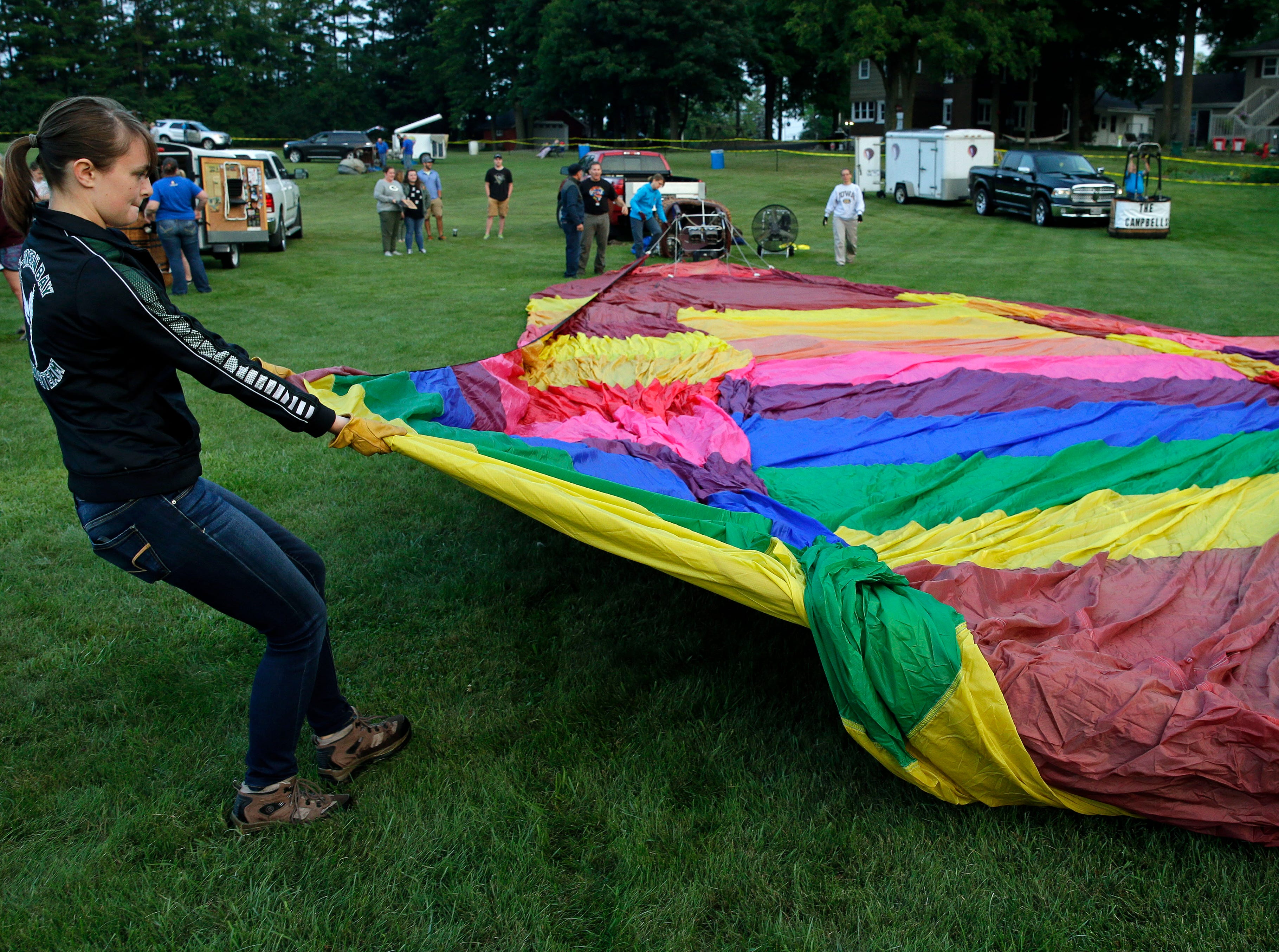 It's a team effort to get a balloon ready to take to the air during the 30th annual Burger Fest Saturday, August 11, 2018, in Seymour, Wis.