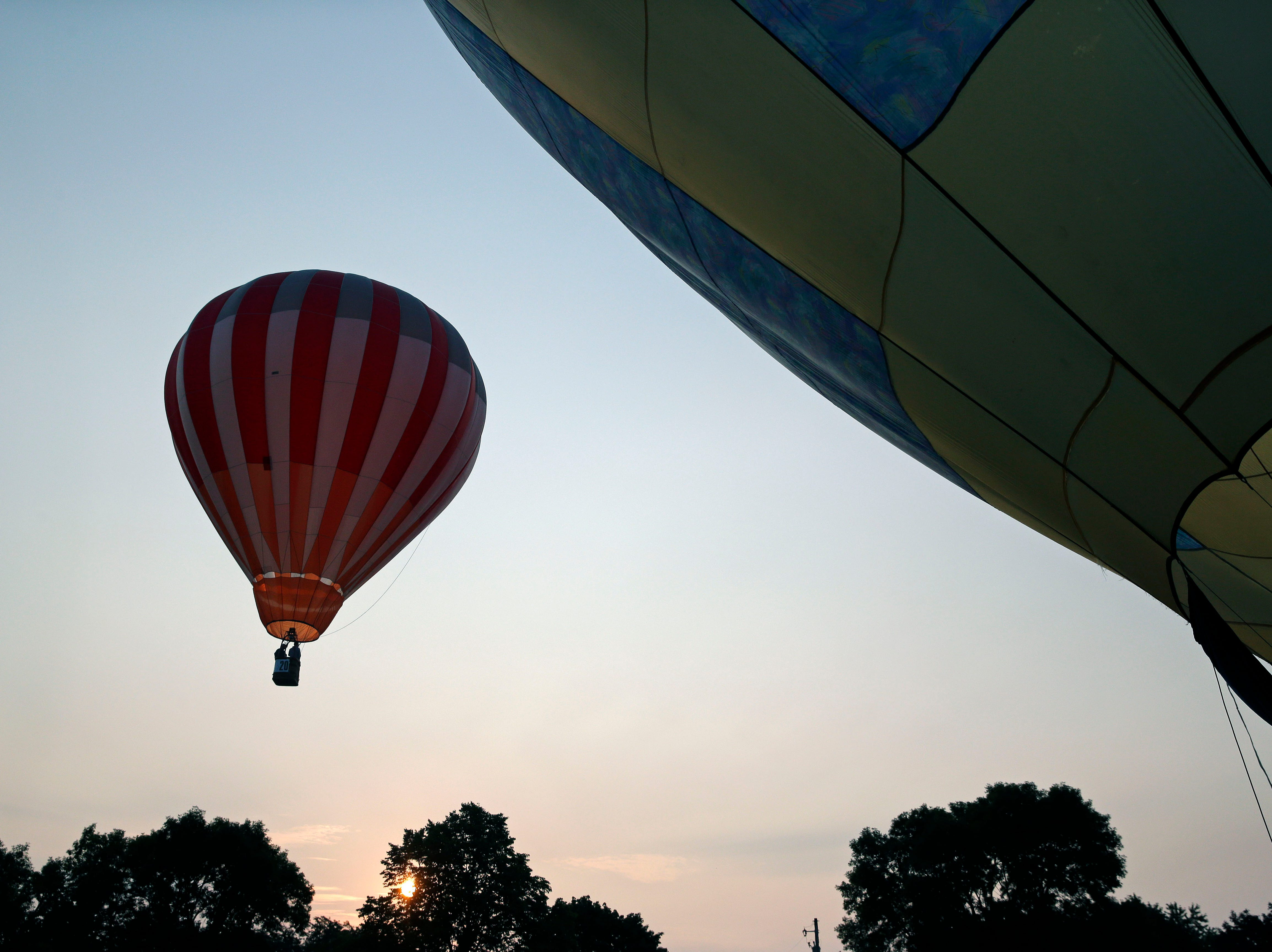 Hot air balloons take to the sky as part of the 30th annual Burger Fest Saturday, August 11, 2018, in Seymour, Wis.