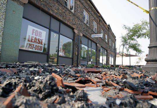 Debris is scattered in front of the Brin Building Saturday in Menasha. The structure burned Friday.