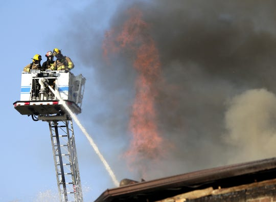 Firefighters battle a blaze Friday at the Brin Building in downtown Menasha.