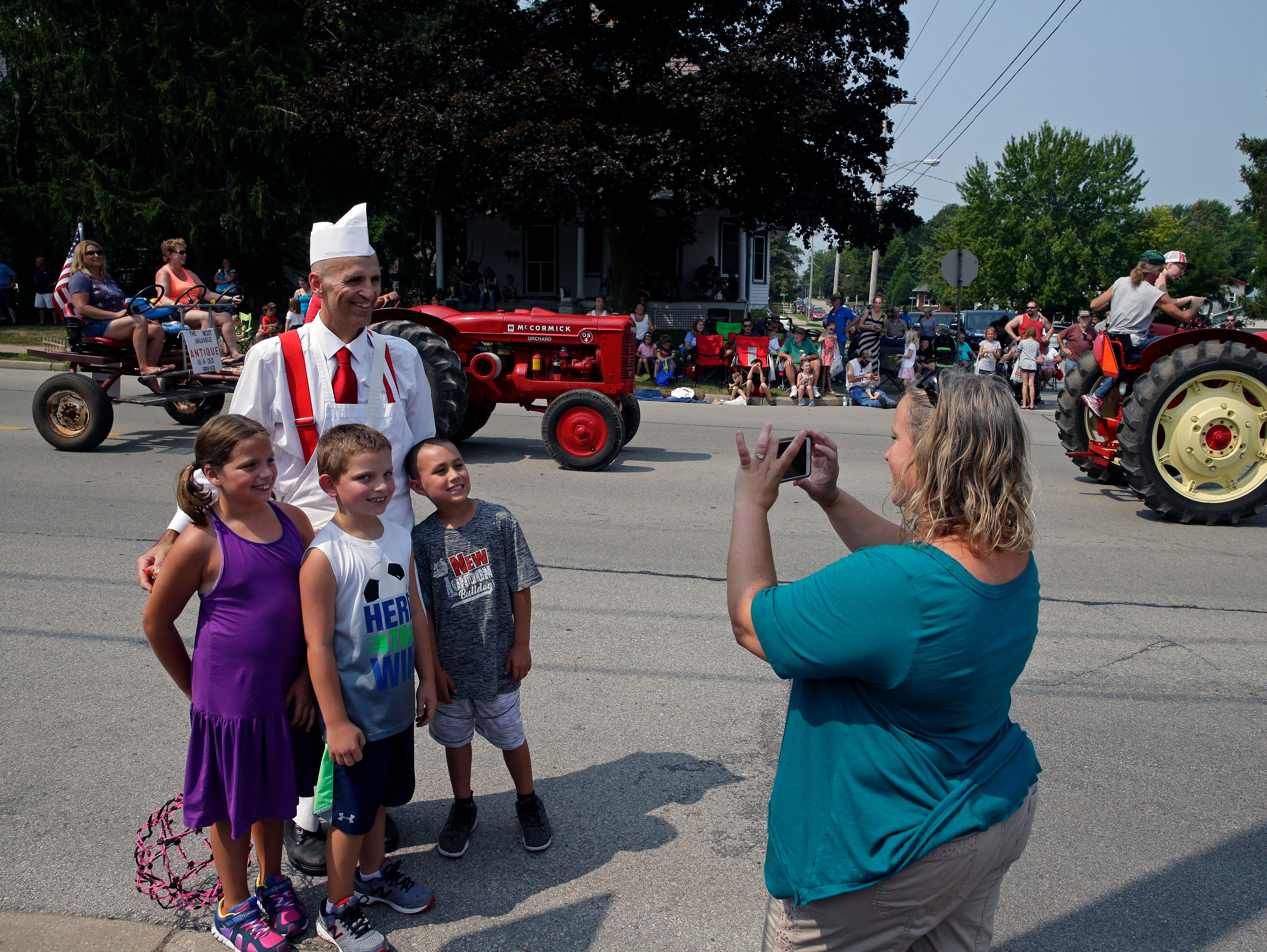 Jennifer Voigt gets a photo of Grace and Ethan Voigt and Jamison Wheelock with Hamburger Charlie during the Hamburger Parade at the 30th annual Burger Fest Saturday, August 11, 2018, in Seymour, Wis.