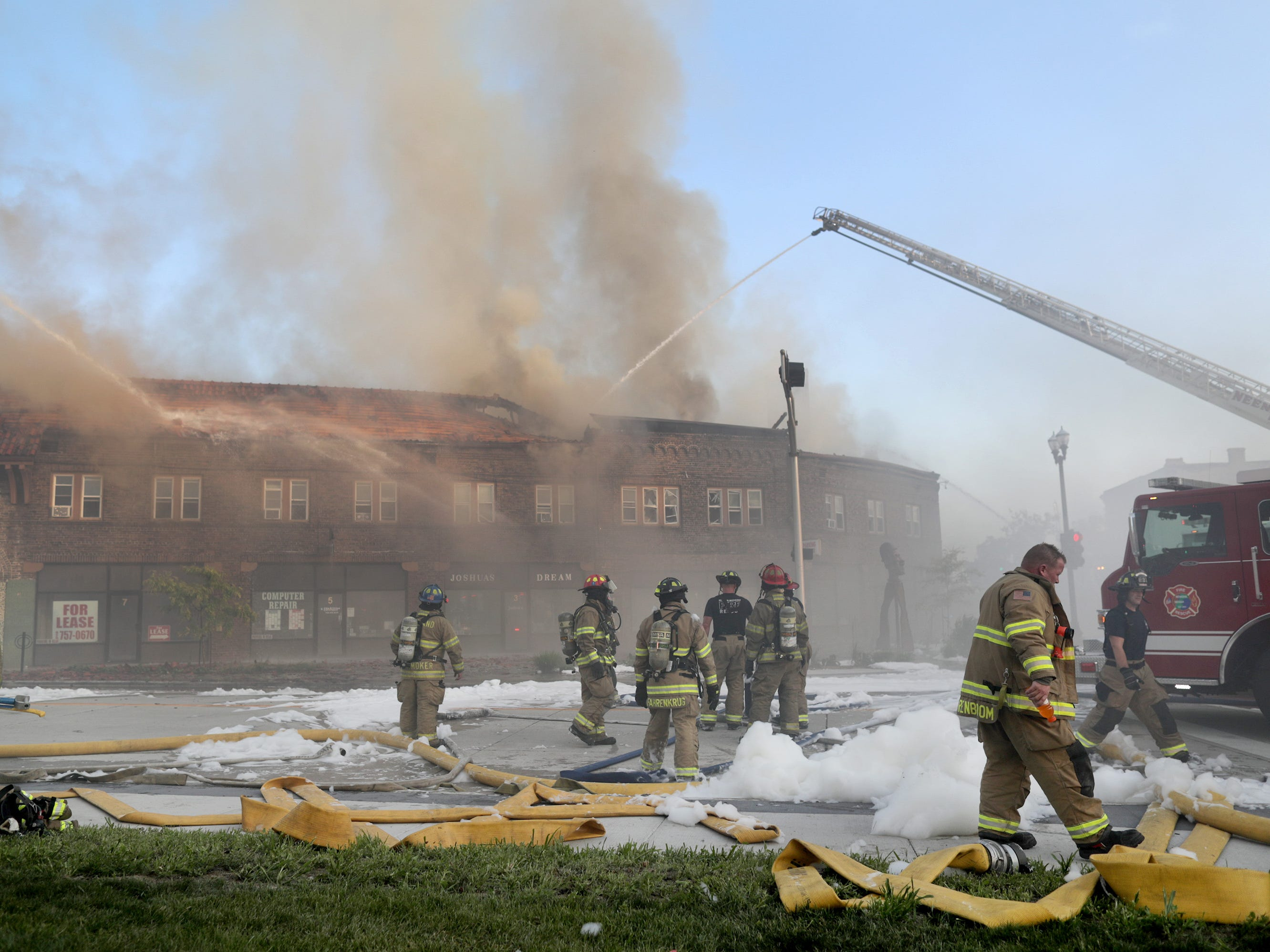 Firefighters from multiple fire departments battle a structure fire in the Brin Building along the block of 1 Main Street on Friday, August 10, 2018, in downtown Menasha, Wis.
